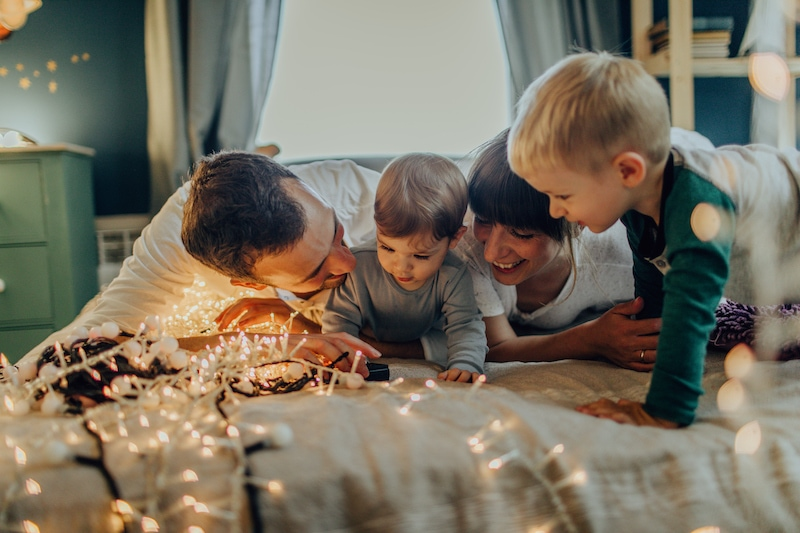 Photo of a young family with two children, enjoying together Holiday season and winter magic in their home