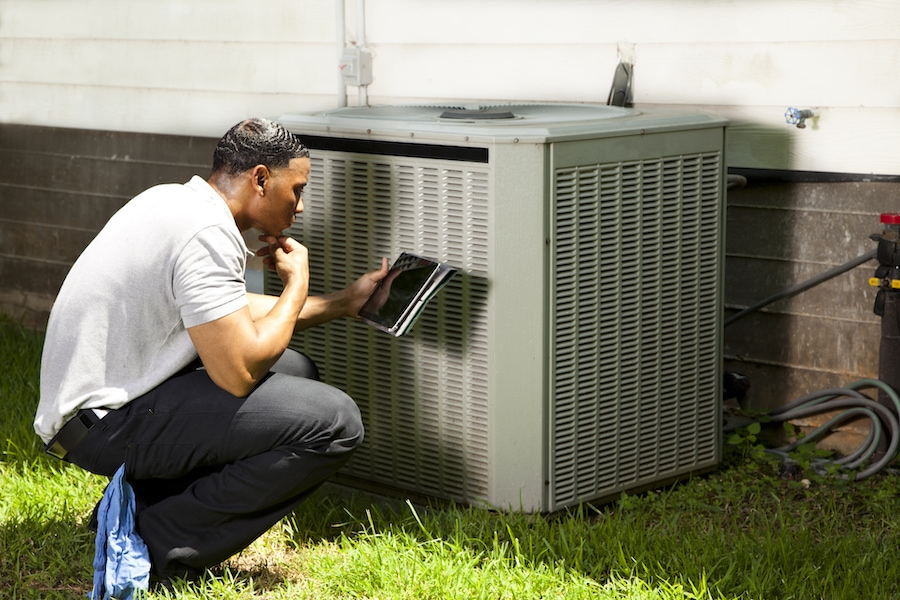 Service technician inspecting air conditioning unit to prepare the system for a hurricane