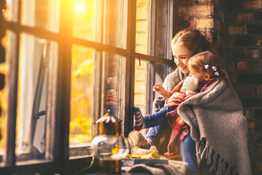 Mother and child enjoying home's heating system during fall weather after scheduling their furnace clean and check appointment
