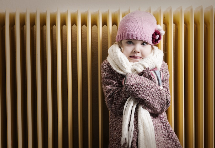 Little girl trying to stay warm while trying to figure out why her home's furnace isn't heating her entire home.