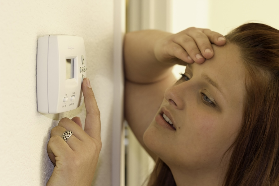 woman trying to figure out why her thermostat is not working while performing troubleshooting tips.