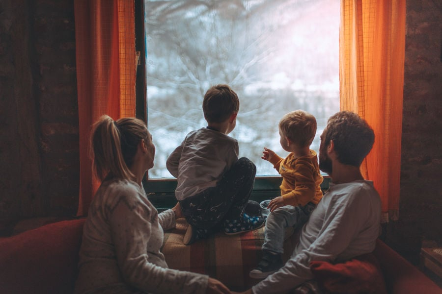 family keeping their heat and staying warm indoors and looking out the window of their home during winter's extreme cold weather.